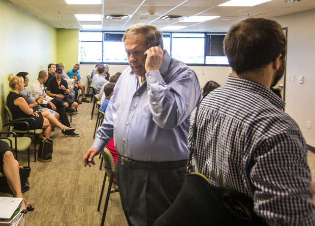 Consultant Jay Brown talks on the phone while medical marijuana applications wait at the City of Las Vegas Department of Planning office,  333 Rancho Drive, on Wednesday, July 23, 2014.  Wednesday ...