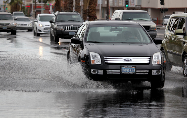A car splashes water on a flooded Charleston Boulevard in Las Vegas on Thursday, July 10, 2014. More rain fell on the valley flooding some roads. (Justin Yurkanin/Las Vegas Review-Journal)