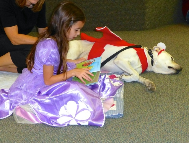 Kendall Boone, 6, dressed for Halloween, reads to one of the Reading with Rascal therapy dogs at Desert Spring United Methodist Church, 120 N. Pavilion Center Drive. The next Reading with Rascal s ...
