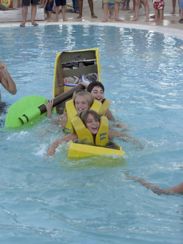 Teammates, from front, 10-year-old Johnathan, 11-year-old Andi, 10-year-old Isaac and 9-year-old Brendan, seem amused as their cardboard boat named The Big Banana begins to sink during the annual  ...