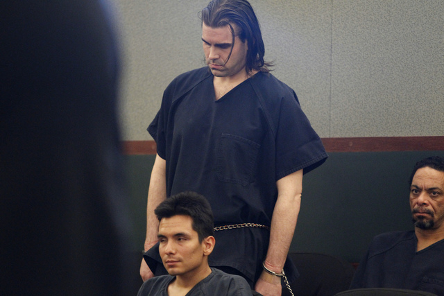 Christopher Reid, center, lowers his head as he waits during his sentencing hearing at the Regional Justice Center in Las Vegas Tuesday, July 22, 2014. Reid pleaded guilty earlier this year to sec ...