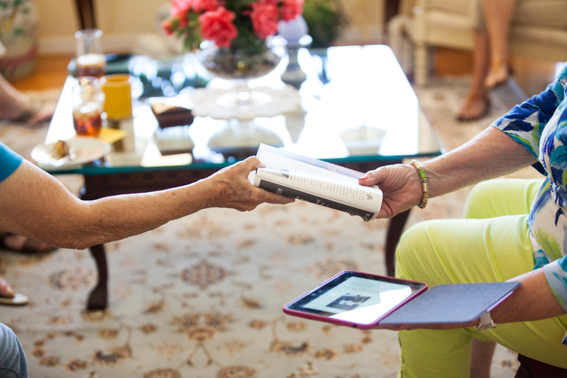 "Ruth Laibson, left, shows her copy of the novel ""The Book Thief"" by Markus Zusak to Ann Ayton, holding a digital eBook copy of the novel, during a group meeting of the Book Leaf Club, of ..."