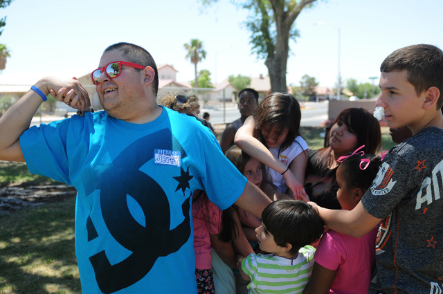 Volunteers Jerry Cahoon, left, and Justin Madrigale, right, play a game of human knot with children from the Vacation Bible School at Upland Bible Church during outdoor activities at Gary Dexter P ...
