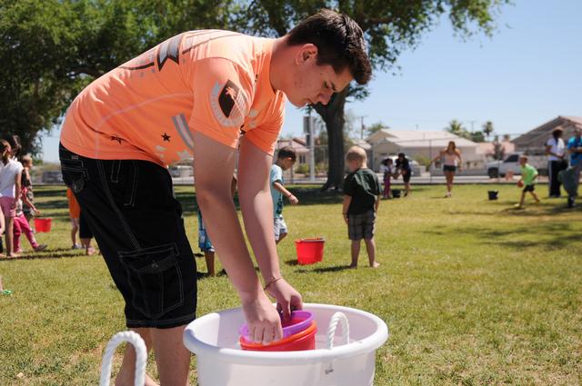 Austin Madrigale, volunteer at Vacation Bible School at Upland Bible Church, fills a bucket of water for a children's activity at Gary Dexter Park in Las Vegas Thursday, June 19, 2014. (Erik Verdu ...