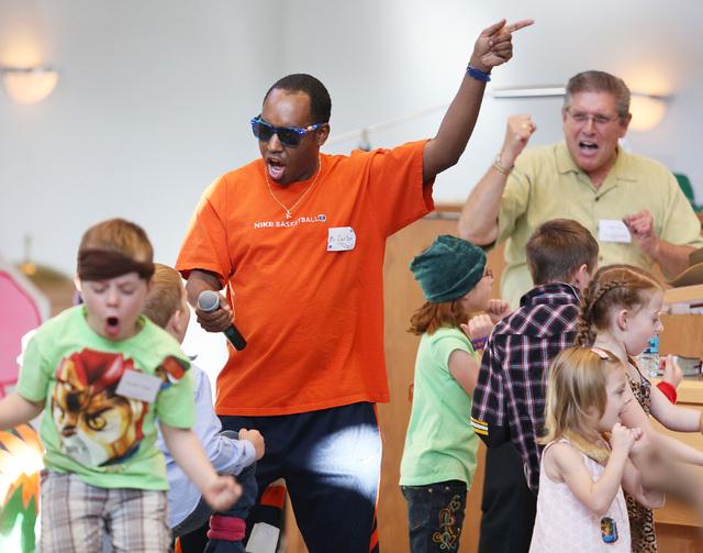 Kaymen Carter (cq), center, leads a children's sing-a-long during vacation Bible school at Green Valley Presbyterian Church Thursday, June 19, 2013, in Henderson. Pastor Ken Harper, back right, si ...