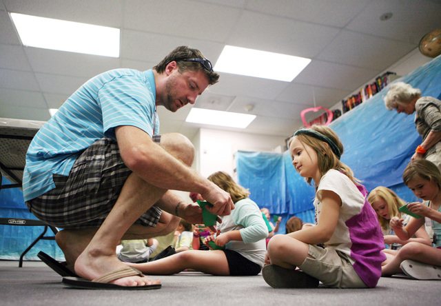 Shawn Hayden, left, helps Delaney Hildt, 6, with a craft during vacation Bible school at Green Valley Presbyterian Church Thursday, June 19, 2013, in Henderson. The camp is a week-long evening pro ...