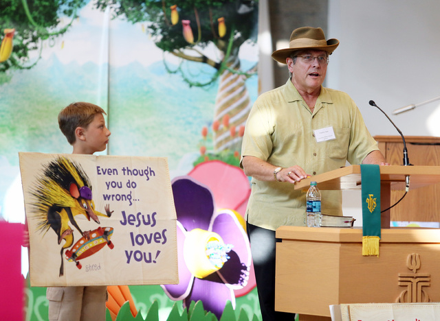 Pastor Ken Harper, right, speaks to children during vacation Bible school at Green Valley Presbyterian Church Thursday, June 19, 2013, in Henderson. Conner Cox holds a sign nearby. The camp is a w ...