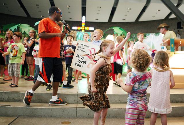 Kaymen Carter (cq), left, leads a children's sing-a-long during vacation Bible school at Green Valley Presbyterian Church Thursday, June 19, 2013, in Henderson. Danica Saeger, 7, front center, dan ...