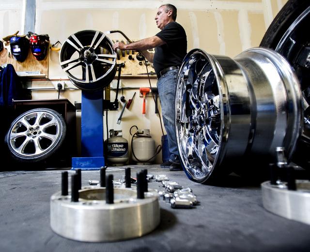 Paul Seidler, owner of Kwicksilver wheel repair business, 50 North Gibson, Suite 150, in Henderson, works on aligning a custom rim on Wednesday, June 25, 2014.  Seidler worked in the White House t ...