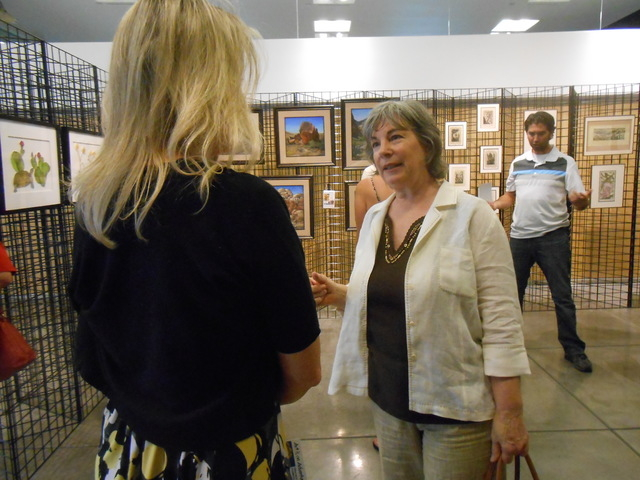 Artist Linda Campbell talks with an attendee July 9 at the reception for the first Red Rock Canyon Artist-in-Residence program exhibition at the Red Rock Canyon National Conservation Area Visitor  ...