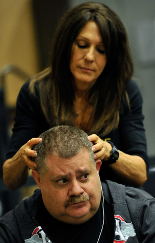 Poker player Al Adler has his head massaged by Ilene Gilbertson as he plays during day 2A/2B of the World Series of Poker Main Event at the Rio hotel-casino on Tuesday, July 8, 2014. (David Becker ...