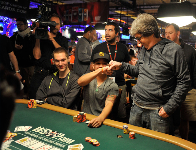 Antonio Luft, right, gets a fist bump from John Adams-Hoang after doubling up during day four of the the World Series of Poker Main Event at the Rio hotel-casino on Friday, July 11, 2014. (David B ...