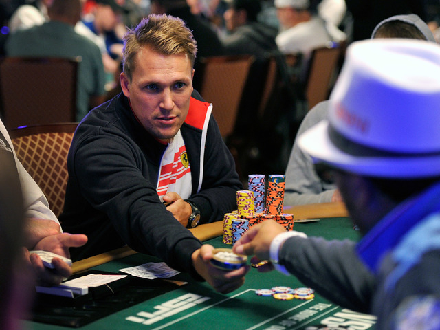 Per Karlsson offers a tobacco pouch to another player during day four of the the World Series of Poker Main Event at the Rio hotel-casino on Friday, July 11, 2014.  Karlsson started the day in eig ...