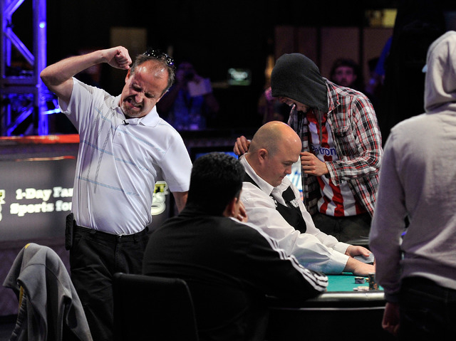 Scott Mahin, left, reacts after busting out on an all in bet against Andoni Larrabe, left, during day 7 of the World Series of Poker Main Event at the Rio hotel-casino on Monday, July 14, 2014. (D ...