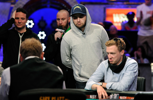 Felix Stephensen, center appears unimpressed with the flop as Bruno Politano, left , and Max Senft look on during day 7 of the World Series of Poker Main Event at the Rio hotel-casino on Monday, J ...