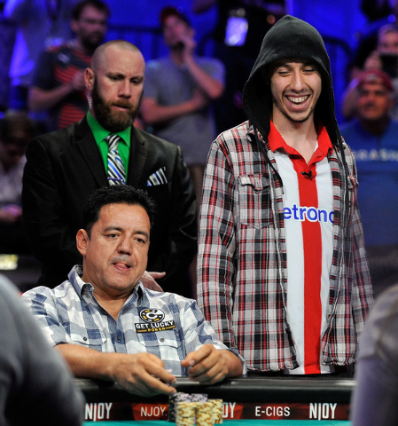 Luis Velador, left, reacts after loosing a hand to Andoni Larrabe, standing at right, during day 7 of the World Series of Poker Main Event at the Rio hotel-casino on Monday, July 14, 2014. (David  ...
