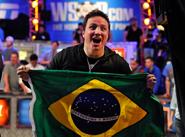 Bruno Politano of Brazil poses with his country's flag after completing day seven of the World Series of Poker Main Event at the Rio hotel-casino on Tuesday, July 15, 2014. Politano survived to th ...