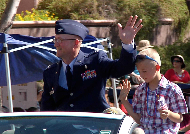 Air Force Col. Brandon T. Snook, commander of the 99th Surgical Operations Squadron at Nellis Air Force Base, greets the crowd as grand marshal of the Annual Summerlin 4th of July Parade. Over 2,5 ...