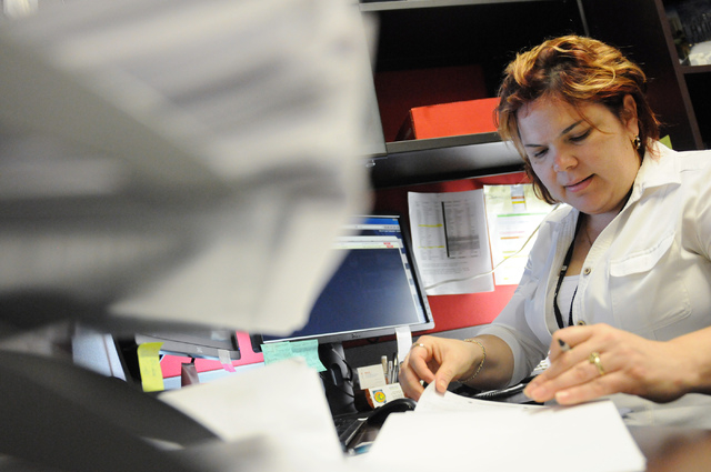 Nubia Licea, a case manager at the One-Stop Career Center, organizes her files. (Erik Verduzco/View)