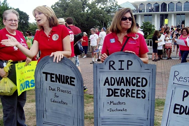 People gather outside the North Carolina General Assembly in Raleigh, NC during summer 2013 to protest the elimination of tenure and extra pay for teachers with advanced degrees in the state. (AP  ...