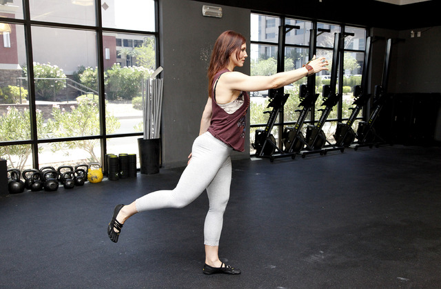 Trainer Laura Salcedo demonstrates the leg swing stretch at CrossFit Mountain's edge in Las Vegas on Tuesday, June 24, 2014. (Justin Yurkanin/Las Vegas Review-Journal).