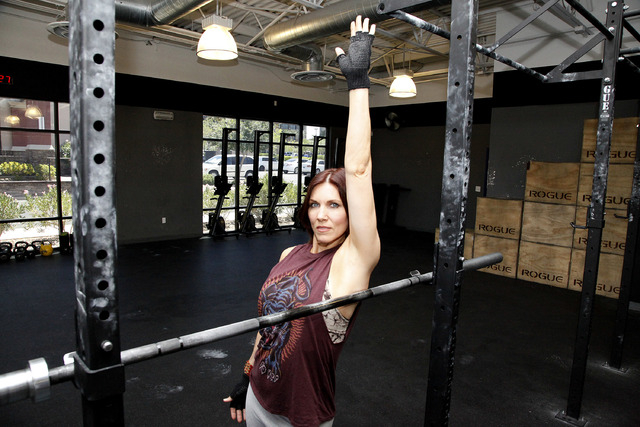 Trainer Laura Salcedo demonstrates the starting position for the lat stretch at CrossFit Mountain's edge in Las Vegas on Tuesday, June 24, 2014. (Justin Yurkanin/Las Vegas Review-Journal).