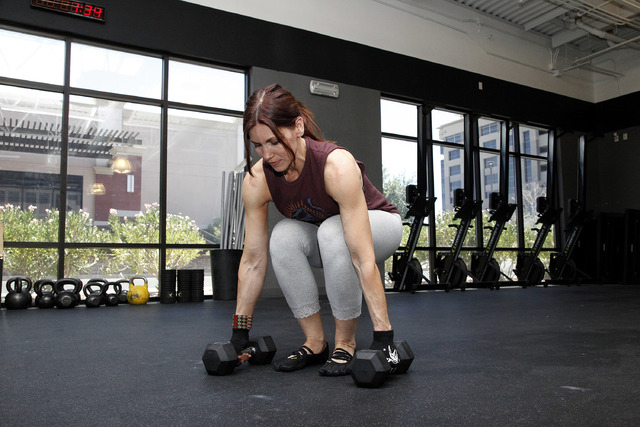 Trainer Laura Salcedo demonstrates the middle position for the dumbbell burpee at CrossFit Mountain's edge in Las Vegas on Tuesday, June 24, 2014. (Justin Yurkanin/Las Vegas Review-Journal).