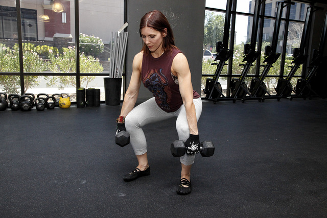 Trainer Laura Salcedo demonstrates the finishing position for the dumbbell deadlift at CrossFit Mountain's edge in Las Vegas on Tuesday, June 24, 2014. (Justin Yurkanin/Las Vegas Review-Journal).