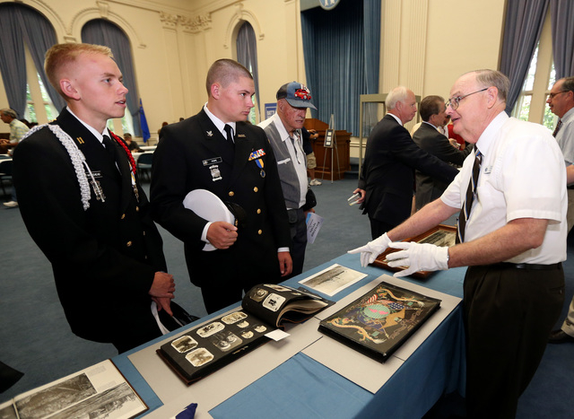 Ron Roberts shows museum pieces to Carson High School NJROTC members Evan Whitehead, left, and Gabriel Pope following the USS Nevada Centennial of Launch ceremony at the Capitol, in Carson City, N ...