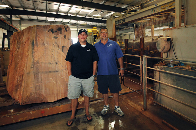 Las Vegas Rock Inc. owner Steve Wickman, right, and Vice President Justin Lindblad pose for a portrait in front of a gang saw at their stone fabrication and cutting facility in Jean on Tuesday, Ju ...