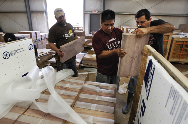 Las Vegas Rock Inc. employees, from left, Scott Collins, Fidel Pina, and Elpidio Avelos load a crate for shipment to Kuwait at their stone fabrication and cutting facility in Jean on Tuesday, July ...