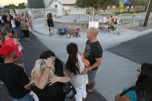 People gather during a candlelight vigil Thursday, June 19, 2014, at the home where two children died in an early morning fire. Firefighters said they found the two children, identified by a famil ...