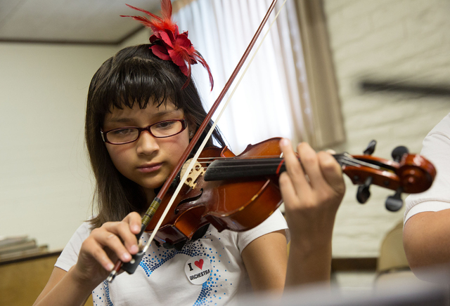 Zitlaly Esparza practices the violin during the Foundation to Assist Young Musicians summer camp at The Church of Jesus Christ of Latter-day Saints, 4201 Stewart Ave., on June 20. The camp is host ...