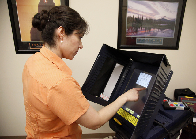Lorena Portillo, an employee with the Clark County Election department, demonstrates how to use the voting machines in the Election Department headquarters in North Las Vegas on Wednesday, July 2, ...
