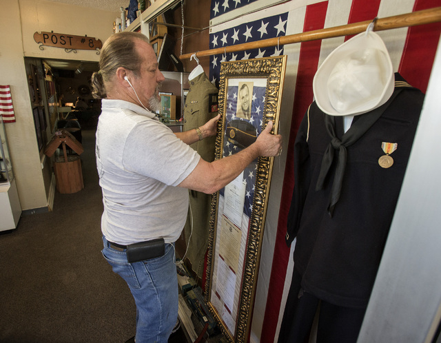 Sons of American Legion Squadron 8 Commander Michael Vines hangs a display of World War I soldier Albert Clark Sr.'s  memorabilia at American Legion Post 8 on Friday, June 27, 2014. (Jeff Scheid/L ...
