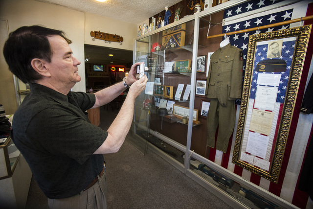 Albert Clark Jr. takes a photo of a collection of memorabilia of his father Albert Clark Sr., he loaned to American Legion Post 8, during the unveiling on Friday, June 27, 2014. The collection inc ...