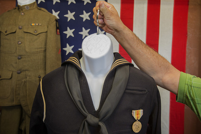 American Legion Post 8 Commander Rod Carlone holds a WWI Navy uniform as seen Friday, June 27, 2014. The post is displaying  a collection of WWI memorabilia donated by families of veterans. (Jeff  ...
