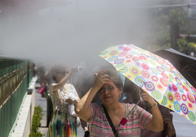 A woman wipes her face near a row of misters in front of the Sugar Factory on Tuesday, July 1, 2014. The temperatures will range from 106-111 over the next few days. (Jeff Scheid/Las Vegas Review- ...