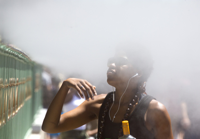 Brianna Taylor cools down near a row of misters in front of the Sugar Factory on Tuesday, July 1, 2014. The temperatures will range from 106-111 over the next few days. (Jeff Scheid/Las Vegas Revi ...
