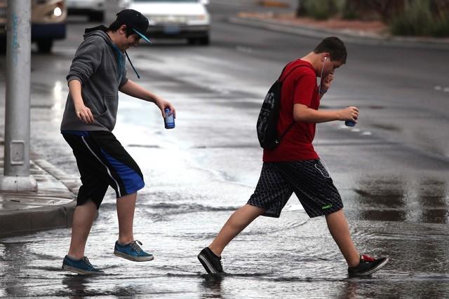 Justin Stonge, left, 14, and Julian Garza, 17, walk across Charleston Boulevard in Las Vegas on Thursday, July 10, 2014. More rain fell on the valley flooding some roads. (Justin Yurkanin/Las Vega ...