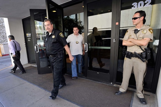 Las Vegas Constable John Bonaventura, left, exits his downtown offices as Las Vegas police look on Tuesday, June 17, 2014. Las Vegas police criminal intelligence section served search warrants in  ...