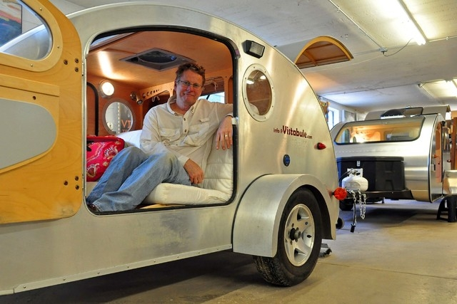 In this June 17, 2014  photo, Bert Taylor sits in an early prototype of his Vistabule camper in a warehouse in Minneapolis, Minn.  Taylor, 63, and a small staff built 12 of the sleek, compact, ret ...