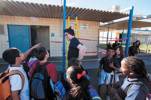 """Students crowd around the principal of Rex Bell Elementary School as he prepares to read """"Diary of a Wimpy Kid"""" in this Nov. 14, 2013. Bell Elementary could be the school that gets rebuilt. (Chase ..."""