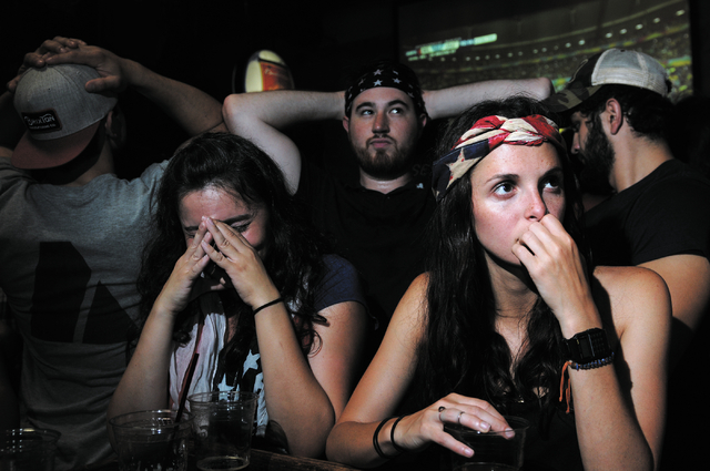 Angela Lais, from right, Ryan Hajdo, and Ashlyn Borstel, react to a goal by Belgium against the United States during a viewing party of the 2014 FIFA World Cup quarter-final soccer game at Crown & ...