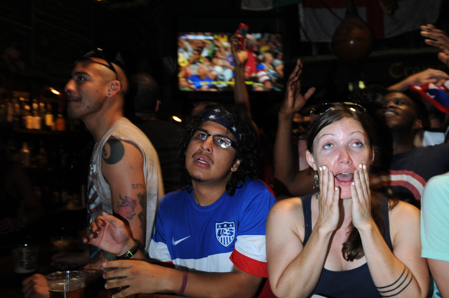 Ismael Gonzales, left,  and Kelly Seibert react to a goal by Belgium against the United States during a viewing party of the 2014 FIFA World Cup quarter-final soccer game at Crown & Anchor British ...