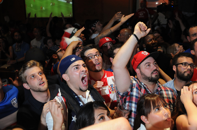 Fans react to a play during the 2014 FIFA World Cup quarter-final soccer game between the United States and Belgium at a viewing party at Crown & Anchor British Pub in Las Vegas Tuesday, July 1, 2 ...