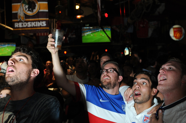 Paul Olesuk, from left, Josh Green, and his friends Matthew Duffy and Jason Waufle, react to a play during the 2014 FIFA World Cup quarter-final soccer game between the United States and Belgium a ...