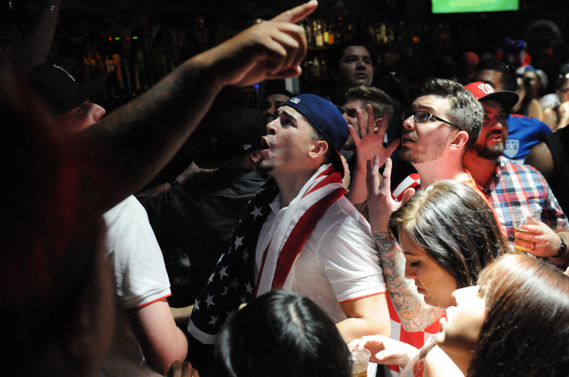 Terry Balboa, center, and his friend Jeremy Trater, right, react to a play during the 2014 FIFA World Cup quarter-final soccer game between the United States and Belgium at Crown & Anchor British  ...