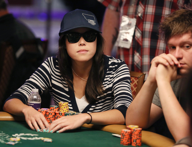 Mikiyo Aoki hold her cards while playing poker in the 2014 World Series of Poker at the Rio hotel-casino Saturday, July 12, 2014, in Las Vegas. The $10,000 No-Limit Hold 'em World Champions ...