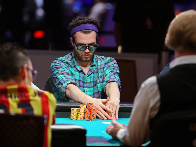 Ben Marsh looks at his cards while playing poker in the 2014 World Series of Poker at the Rio hotel-casino Saturday, July 12, 2014, in Las Vegas. The $10,000 No-Limit Hold 'em World Champio ...